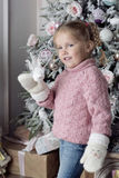A child stands near a Christmas tree. Smiling girl wearing warm mittens Stock Photography