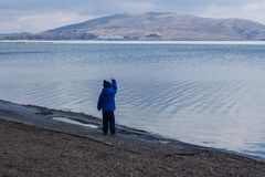 Child stands next to the sea in spring stock photo