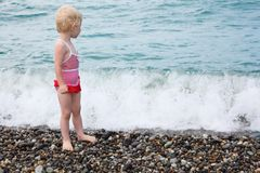 Child stands on pebble beach Stock Photo