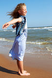 Child stands on the shore of the ocean with arms outstretched. Happy child stands on the shore of the ocean with arms outstretched Royalty Free Stock Images