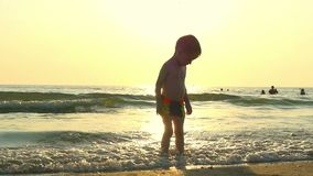 The child stands in the water on the sea beach, in the incoming waves, against the background of a decline at a slowed. Pace. Slow motion stock video