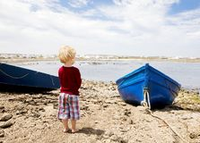 Child Stares Out Over a Bay with Fishing Boats. A barefooted child in a red shirt and checkered shorts is seen from behind staring out over a rocky fishing bay Royalty Free Stock Photo