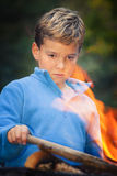 Child staring at campfire. Staring at the flames young boy trying to keep the fire going by putting a piece of dry wood Royalty Free Stock Photos