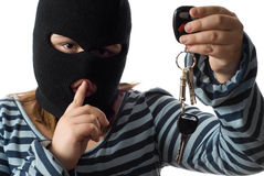 Child Stealing Car Keys. Closeup view of a child stealing some car keys, isolated against a white background stock photo