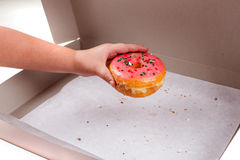 Child stealing the last donut from the box Royalty Free Stock Image