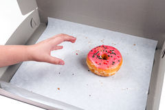 Child stealing the last donut from the box Stock Photo