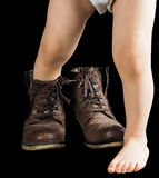 Child stepping out of a pair of too big untied and unpolished boots. Toddler boy, towards black background out of fathers brown leather boots stock photography