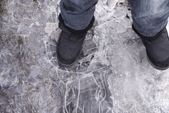 Child steps on frozen puddle with thin ice Royalty Free Stock Image