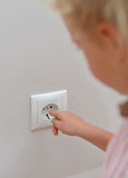 Child sticks fingers in the socket. Royalty Free Stock Images