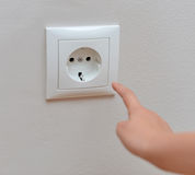 Child sticks his fingers in the socket. Stock Image