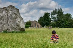 Child at stone circle site in England, Avebury. Child sitting in grass near a megalithic standing rock at ancient site of stone circle, a house or chapel in the Royalty Free Stock Images