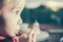 Child with straw in her mouth - Retro look Stock Image