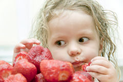 Child with a strawberry Stock Images