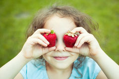 Child with strawberry eyes Stock Photos