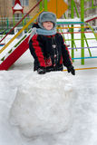 Child on street on walk. Child on street plays with snow Royalty Free Stock Photo