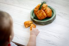 Child stretches his hand to a plate with scone biscuits. stock photo