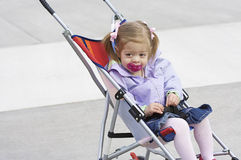 Child in a stroller. A young girl riding in a stroller with a pacifier in her mouth Stock Photos