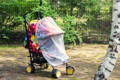 Child in stroller covered with protective net during walk. Baby carriage with anti-mosquito white cover. Midge. Protection for children during outdoor walking royalty free stock photography