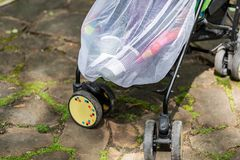 Child in stroller covered with protective net during walk. Baby carriage with anti-mosquito white cover. Midge. Protection for children during outdoor walking stock photography