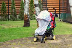 Child in stroller covered with protective net during walk. Baby carriage with anti-mosquito white cover. Midge. Protection for children during outdoor walking stock images