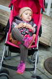 Baby in stroller. Child in a stroller on the street eating cookies stock image