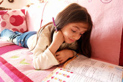 Child struggles in math. 8 years old girl studies math but the exercise is difficult one royalty free stock photo