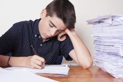 Child student on the desk. With stacked papers stock image