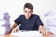 Child student on the desk. With stacked papers stock photos