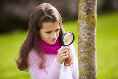 Child studing biology. Looking to a tree trunk stock image