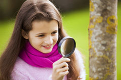 Child studing biology. With a magnifier glass royalty free stock photo