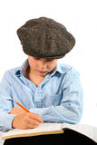 Child studying. Portrait of a young boy studying or reading a book. White background royalty free stock photography