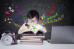 Child studying with books and formula Royalty Free Stock Images