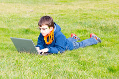 Child studying on the grass. Child lying in the grass studying with a laptop Stock Images