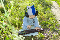 Child studying keyboard Outdoors. Royalty Free Stock Photo
