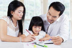Child studying with parents in home Stock Photo