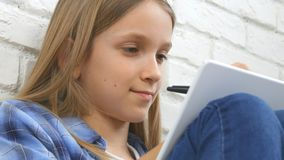 Child Studying on Tablet, Girl Writing for School Class, Learning Doing Homework royalty free stock images