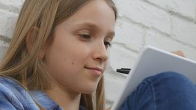 Child studying on tablet, girl writing for school class, learning doing homework.  stock video footage