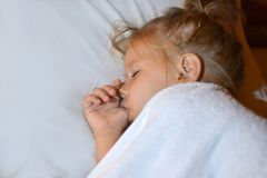 The child sucks a finger in bed before bedtime and during sleep royalty free stock photos
