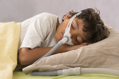 Child suffering from Sleep Apnea, wearing a respiratory mask