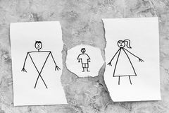 Child suffers from a divorce. Torn sheet of paper with drawn man, woman and child on grey background top view copy space. Child suffers from a divorce. Torn stock image