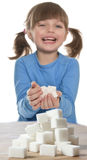 Child with sugar cubes. Little girl  with sugar cubes and white background Royalty Free Stock Images