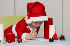 Child in a suit of Santa Claus writing a letter Royalty Free Stock Photos