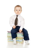 Child in suit and sitting on the heap of books Stock Photos