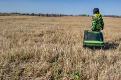 Child with the suitcase goes. Through a big yellow autumn field. Rear view Royalty Free Stock Photography