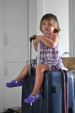 Child on the suitcase. Child waiting on the suitcase Stock Photo