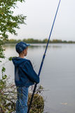 Child on a summer fishing on the shore Stock Photography