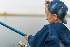 Child on a summer fishing on the shore. Attentive , focused, serious child is on a summer fishing on the river with a fishing rod in his hands Royalty Free Stock Images