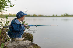 Child on a summer fishing on the shore Stock Images