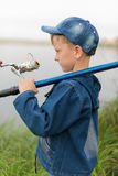 Child on a summer fishing on the shore. Attentive , focused, serious child is on a summer fishing on the river with a fishing rod in his hands Stock Photography