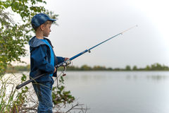 Child on a summer fishing on the shore. Attentive , focused, serious child is on a summer fishing on the river with a fishing rod in his hands Royalty Free Stock Photos